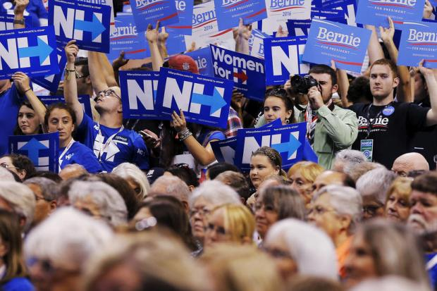 Supporters of U.S. Democratic presidential candidate Hillary Clinton and U.S. Senator Bernie Sanders hold signs at the New Hampshire Democratic Party State Convention in Manchester